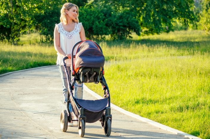 Tips for new mums - new mum walking in the park with newborn baby in pram. tips for new mums
