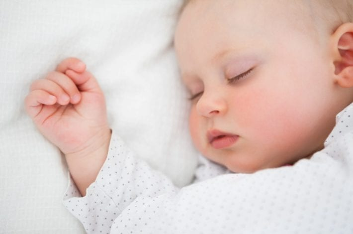 newborn baby fast asleep showing face and hand