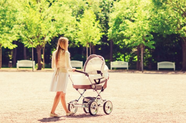 mother walking in the park with her newborn baby in a pram