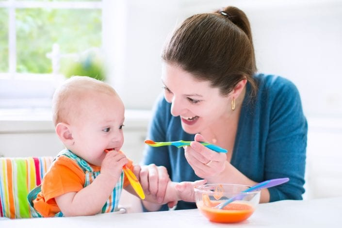 Mother giving baby first foods - weaning