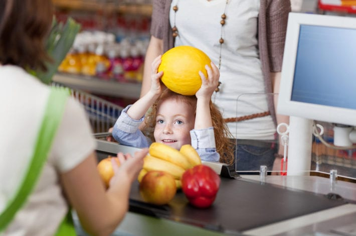 child helping with fruits at the supermarket