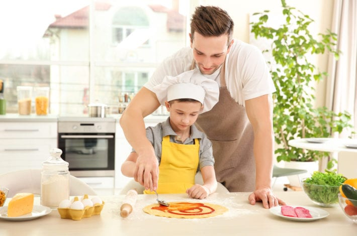 father and son making pizza
