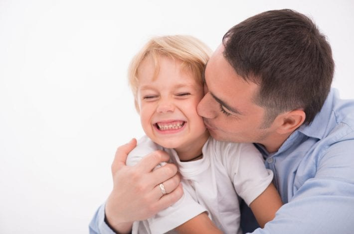 father kissing son praising him