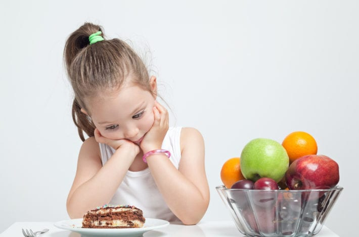 girl looking at cake instead of fruits