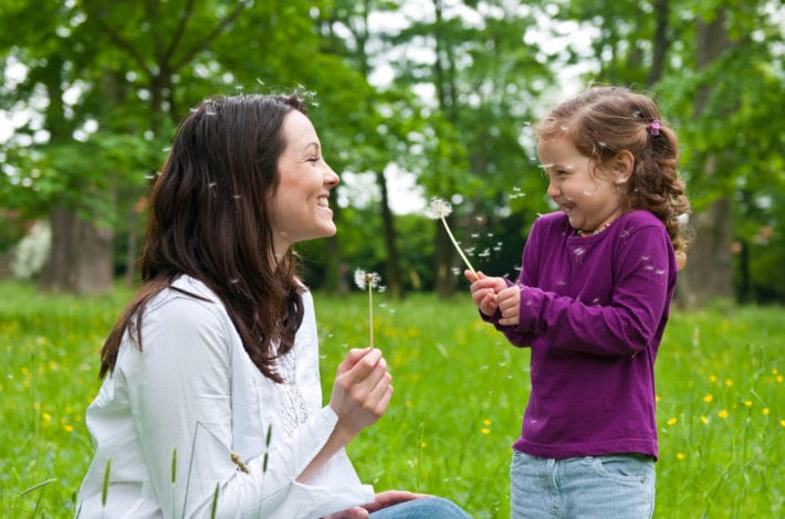 mother and daughter enjoying time together outdoors with dandelion