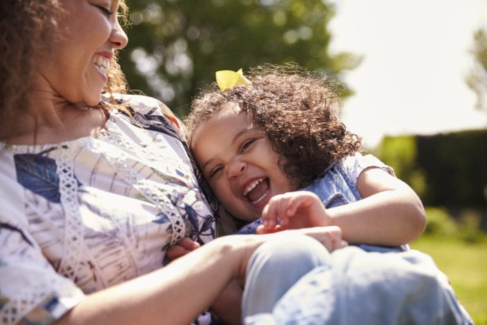 mother tickling her young daughter in the park - mother and daughter laughing