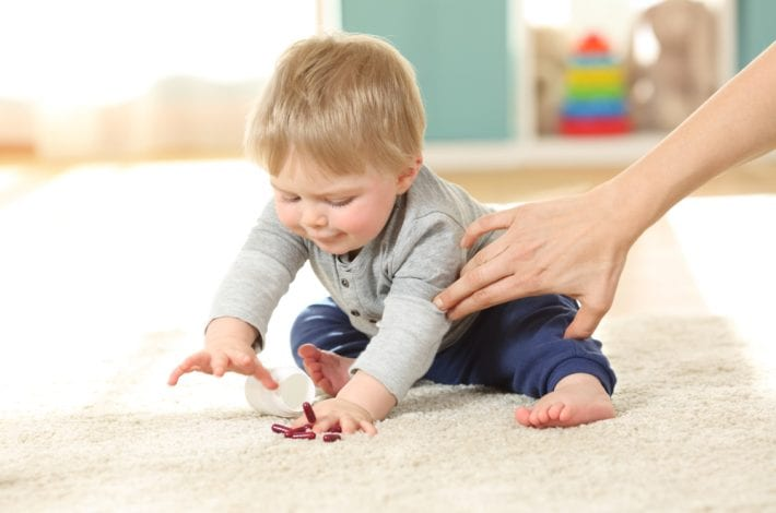 toddler about to eat pills - dangers in the home
