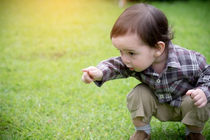toddler boy pointing and discovering things outdoors
