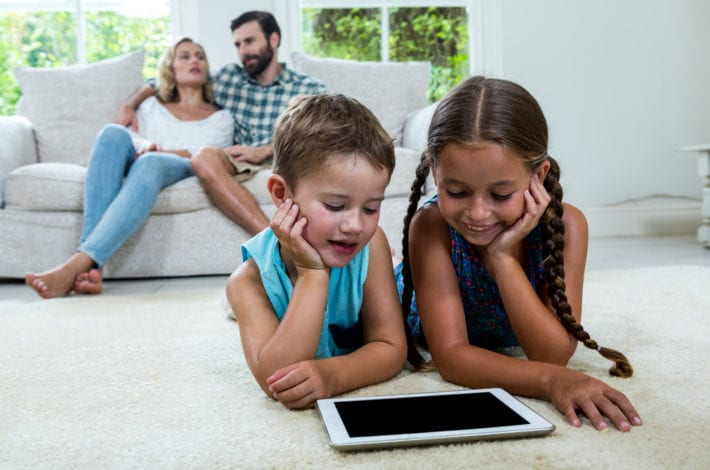 child safe online - children on ipad with parents on sofa